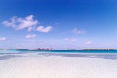 Blauwe hemel over wit zandig strand stock foto