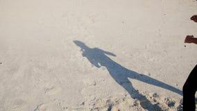 Op het zand kunt u de schaduw, het silhouet van een atletisch meisje zien, dat het opheffen van de benen, vervult uitvoert stock videobeelden