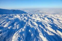 Op ijs en sneeuw opent de behandelde bergbovenkant een mooie mening van de grenzeloze blauwe hemel, dichte geweven mist in de win Royalty-vrije Stock Afbeeldingen
