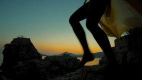 Op mooie zonsondergang daalt het silhouet van een vrouw in lichte kleding stock footage