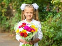 Op portret van zevenjarig schoolmeisje met een boeket van bloemen Stock Fotografie