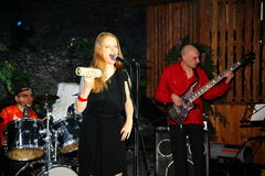 Op stadium, de de groepsgroene munt en de zanger Anna Malysheva van de musici pop-rots Rood Het rode geleide Glam-Rotsmeisje zing Stock Afbeeldingen