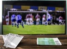 Op TV zijn er een liga en euro van kampioenen op voetbal op de kaartjes van de lijstbookmaker ` s, tarieven op sporten stock afbeeldingen