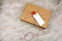 Cardboard box with cloth pin with red heart and empty white label with place for text marble background. Top view cardboard box with cloth pin with red heart and royalty free stock images