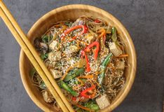 Op view of an oriental wooden plate with vegan dish of glass noodles. Top view of an oriental wooden plate with vegan dish of glass noodles, tofu, fresh