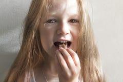 Op wit mooi meisje die als achtergrond met lange haar het glimlachen dageraadochtend suikergoed eten royalty-vrije stock afbeeldingen