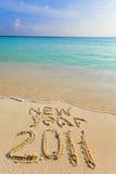 Op zand bij oceaanrand wordt het geschreven 2011 Stock Foto's