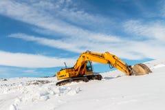 Op zwaar werk berekend die bouwmateriaal bij het werkplaats en de winter wordt geparkeerd stock foto's