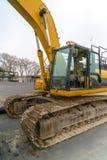 Op zwaar werk berekend die bouwvoertuig op de weg wordt geparkeerd stock afbeelding