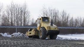 Op zwaar werk berekende machines die aan wegbouwwerf werkt stock footage