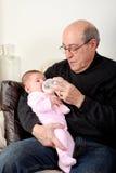 Opa die babymeisje met de fles grootbrengt Stock Afbeeldingen