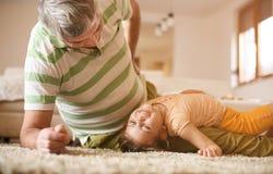 Opa en kleindochter het spelen Stock Afbeeldingen