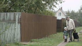 Opa en kleinzoon die in poort komen. stock footage