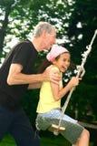 Opa en meisje door schommeling stock afbeeldingen