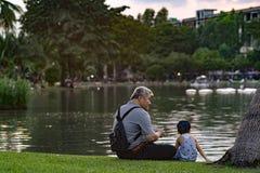 Opa en neef het ontspannen in chatuchakpark Stock Afbeeldingen