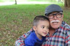Opa het vertellen verhalen aan kleinzoon stock foto