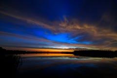 Opacifiez dans l'aube de matin allumée par ciel, reflétée dans l'eau Images libres de droits
