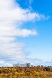 Opacifiez l'avant en ciel au-dessus des bois et des maisons jaunes Photo stock
