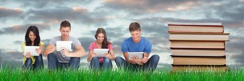 Opanowany wizerunek ucznie studiuje z pastylkami obok książek obrazy stock