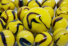 Opaque yellow and brown glass marbles royalty free stock image