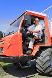 Oparation dell'agricoltore della montagna una mietitrice del fieno in un cappuccio Fotografia Stock