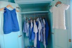 Opatrunkowa szafa z błękitów ubraniami w szafie Zdjęcie Stock