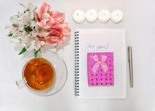 Opatrunkowy stół z women&-x27; s akcesoria Wizerunek różowy prezenta pudełko z bukietem Alstroemeria kwitnie, świeczki, filiżanki zdjęcie stock