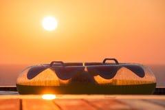 Opblaasbaar zwem Ring die op een Zwembaddek Pomos-overzees met Zon het Plaatsen overzien Stock Afbeeldingen