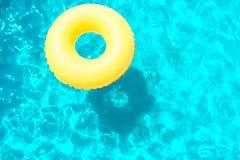 Opblaasbare ring die in de pool op een zonnige dag zwemmen stock fotografie