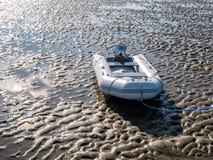 Opblaasbare rubberboot met buitenboordmotor op zandvlakte van Waddensea at low tide, Nederland stock afbeeldingen