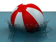 Opblaasbare strandbal die in het water valt Stock Afbeelding