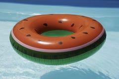 Opblaasbare watermeloenring in pool op zonnige dag stock afbeeldingen