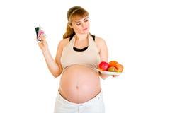 Opción de fabricación embarazada entre las píldoras y las frutas Foto de archivo libre de regalías