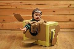 Opción de la profesión Pequeño niño en el piloto Costume Dreaming Of que pilota el avión fotos de archivo