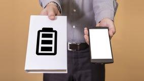 Opción entre el libro y la vida de batería del teléfono móvil Fotos de archivo libres de regalías