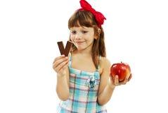 Opciones de la dieta sana - niña con la manzana y el chocolate Foto de archivo