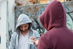 Opdringer en drugverslaafde die geld en drug ruilen Stock Afbeeldingen
