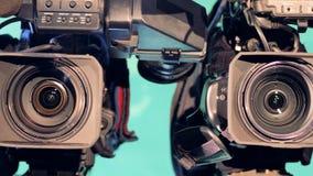 Opeenvolgende dichte omhooggaand van drie videocamera's` lenzen stock videobeelden