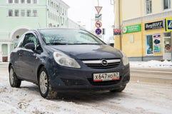 Opel Astra in de winter dichtbij het huis wordt geparkeerd dat Stock Afbeelding