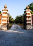 The open gate with two pine cones. The opem gate with two marble pine cones in the south of France during summer royalty free stock photography