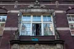 Open在格但斯克主要镇变老了与浅浮雕的破旧的窗口在其中一个历史建筑 库存图片