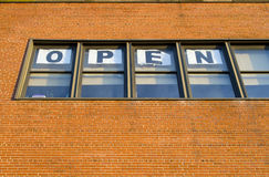 Open. Sign in the windows on the brick wall royalty free stock image
