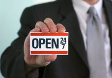 Open 24/7. Man holding a sign that says Open 24/7. Online support, store opening, and other business-related customer service concepts Royalty Free Stock Photo