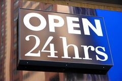 Open 24 Hours. A sign indicating a store open 24 hours stock photo