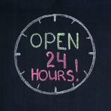 Open 24 hours!. The dial with text Open 24 hours!, drawn on a blackboard Stock Photo