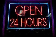 Open 24 hours neon sign. In store window at night Stock Image