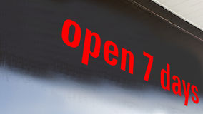 Open 7 days. Shop sign open 7 days bright red letters, black background with lower highlights Stock Photography