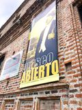 Sign outside of the Museo Remigio Crespo Toral, Cuenca Ecuador. Open Abierto Sign hanging on the red brick facade of the museum as visitors enter this landmark royalty free stock photo