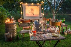 Open air cinema with retro projector in summer garden Stock Image