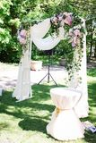 Open air decorated area for the wedding ceremony with a wooden arch decorated with fresh flowers and beige material. Beautiful wed. Ding set up. Wedding ceremony Royalty Free Stock Images